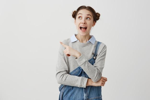 Donna contenta in tuta di jeans prestando attenzione a qualcosa di incredibile che mostra il dito indice a lato con la bocca aperta. giovane femmina felice di presentare il suo posto preferito. copia spazio