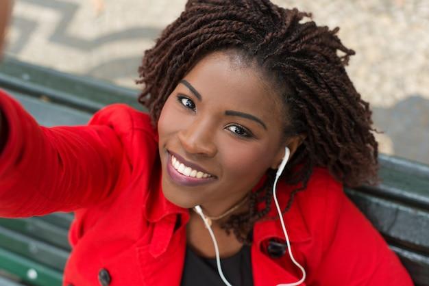 Donna contenta nel sorridere delle cuffie