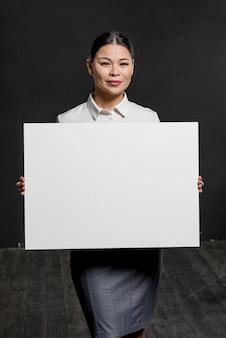 Donna convenzionale che tiene foglio di carta bianco