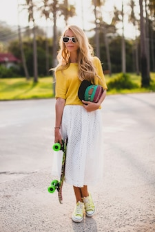 Donna cool hipster con skateboard e cappuccio in posa sorridente in vacanza