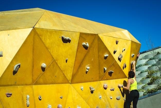 Donna coraggiosa che allena i suoi muscoli d'arrampicata su una parete da arrampicata al sole.