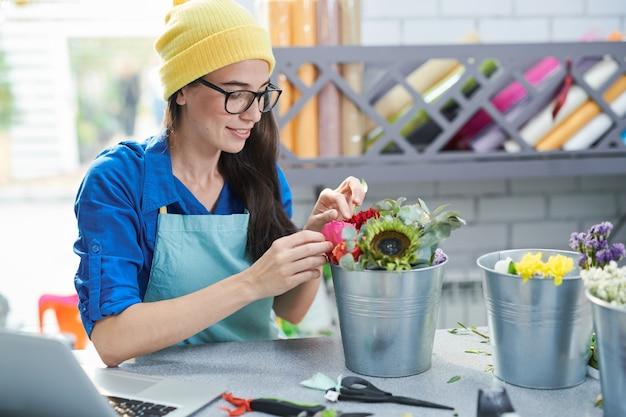Donna creativa che organizza i fiori