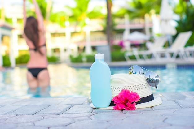 Donna, crema solare, cappello, occhiali da sole, fiori e torre vicino alla piscina