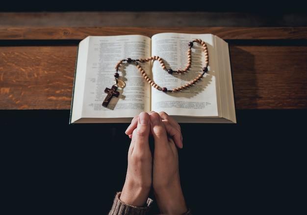 Donna cristiana che prega nella chiesa. mani incrociate e sacra bibbia sullo scrittorio di legno.