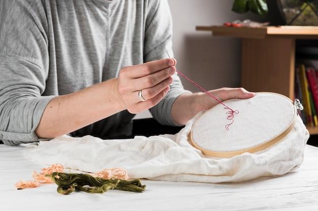 Donna cucito ricamo con filo rosso sul cerchio