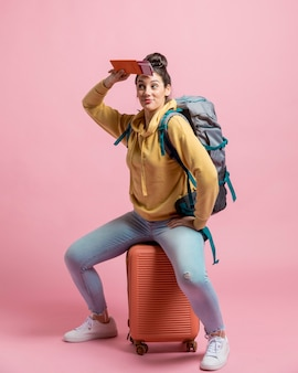 Donna curiosa che si siede sul suo bagaglio
