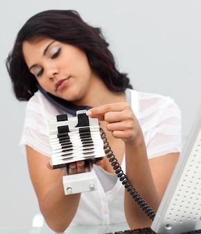 Donna d'affari al telefono e guardando un titolare dell'indice