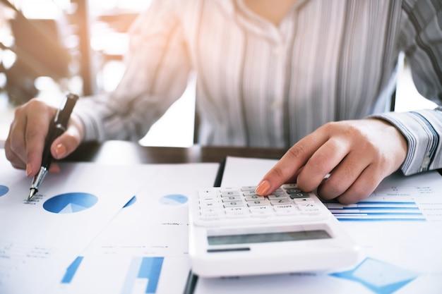 Donna d'affari analizzando i grafici di investimento e premendo il calcolatore