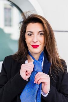 Donna d'affari che annoda cravatta blu