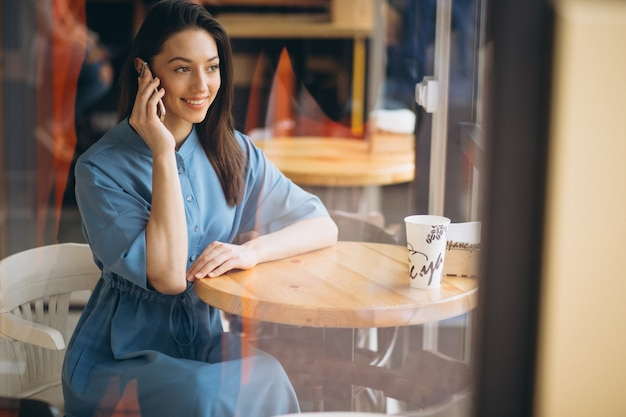 Donna d'affari con caffè e parlando al telefono in un caffè