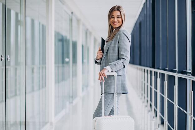 Donna d'affari con i bagagli di viaggio in aeroporto, con laptop