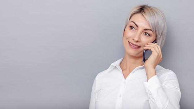 Donna d'affari copia-spazio parlando al telefono