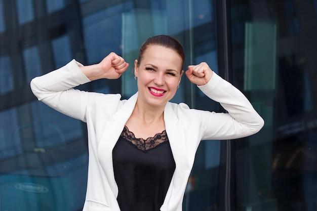 Donna d'affari di successo felice con le braccia in alto celebrando, sorridendo. sì, l'ho fatto! gesturing molto felice giovane donna sorridente allegra in abiti formali, giacca.