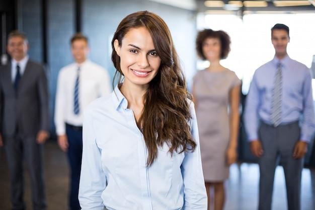Donna d'affari di successo sorridente mentre i suoi colleghi in piedi dietro di lui in ufficio