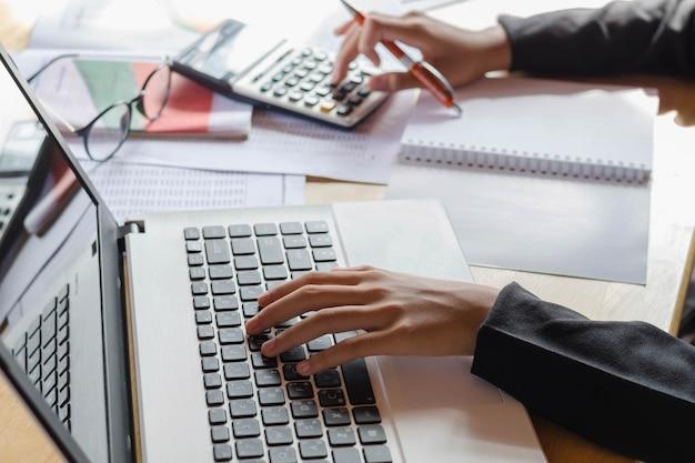 Donna d'affari e computer portatile di concetto di contabilità di affari con il calcolatore sull'area di lavoro della tavola