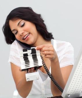 Donna d'affari etnica sul telefono e guardando un titolare dell'indice