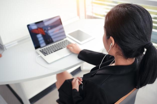 Donna d'affari fare una pausa dal lavoro completato elencando la musica con effetto luce solare