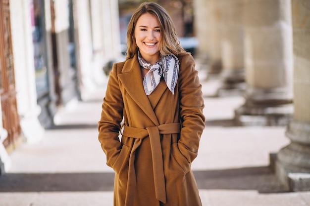 Donna d'affari felice in cappotto in strada