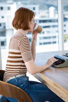 Donna d'affari hipster seduto una scrivania, bere caffè e scrivere