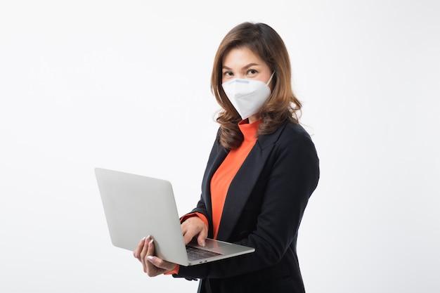 Donna d'affari in abito indossare in possesso di un computer e utilizzare una maschera per proteggere dal coronavirus