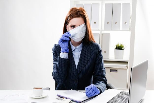 Donna d'affari in maschera e guanti di gomma sul posto di lavoro