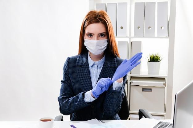Donna d'affari in una maschera sul posto di lavoro indossa guanti di gomma