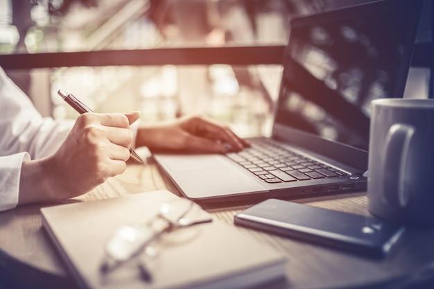 Donna d'affari, lavorando con grafico aziendale e portatile
