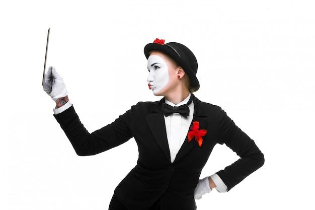 Donna d'affari nell'immagine mime tenendo tablet pc