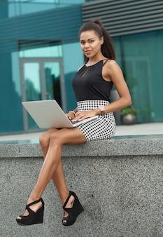 Donna d'affari nera seduta nella città finanziaria, utilizzando un computer portatile, riflessivo, soleggiato all'aperto. donna afroamericana professionale che usando tecnologia, stile di vita di lavoro.