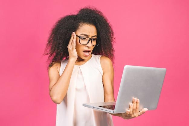 Donna d'affari o studentessa stupita scioccata, in posa sul rosa. mock up copia spazio. lavorando su computer pc portatile.