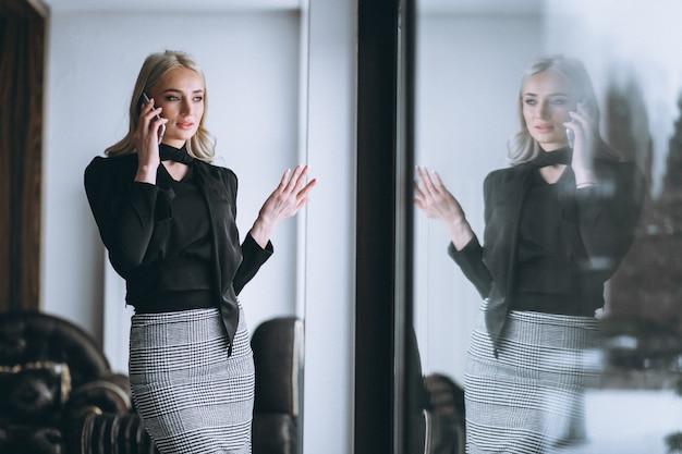 Donna d'affari parlando al telefono dalla finestra