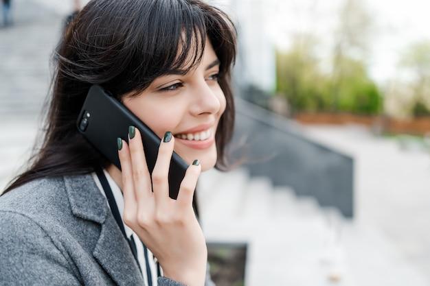 Donna d'affari parlando al telefono e sorridente all'aperto