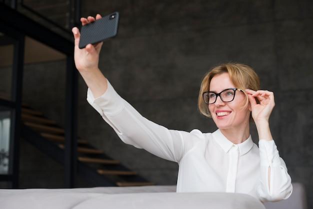 Donna d'affari prendendo selfie con smartphone