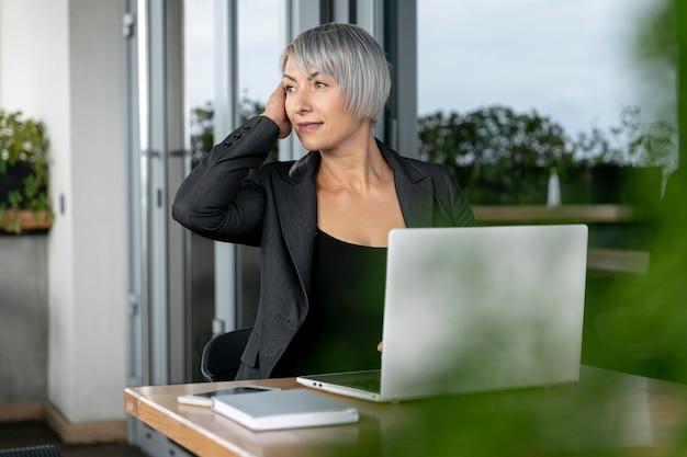 Donna d'affari seduto e guardando lontano
