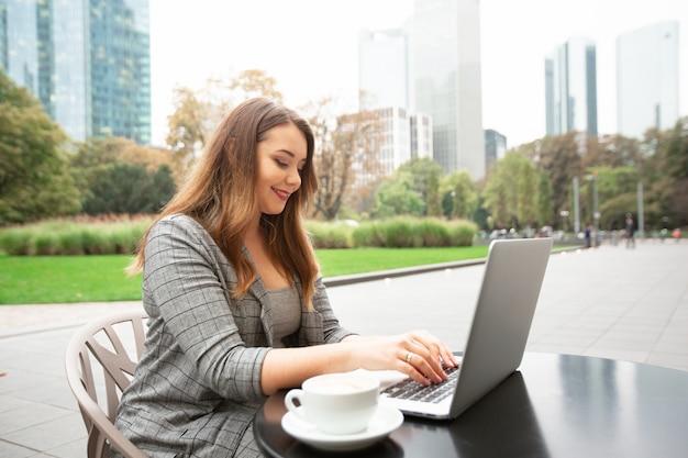 Donna d'affari seduto in una caffetteria sulla strada della città, lavorando a un computer portatile.