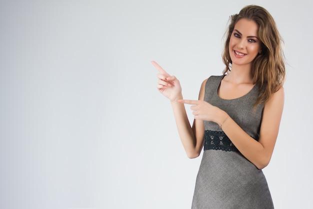 Donna d'affari sorridente che punta il dito sullo spazio della copia. ritratto isolato