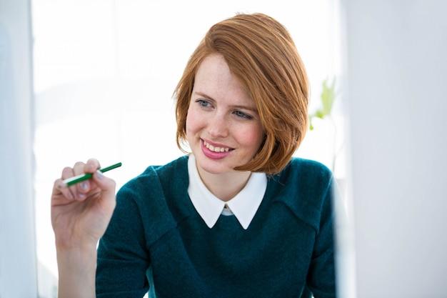 Donna d'affari sorridente hipster, seduto alla sua scrivania, guardando il suo computer