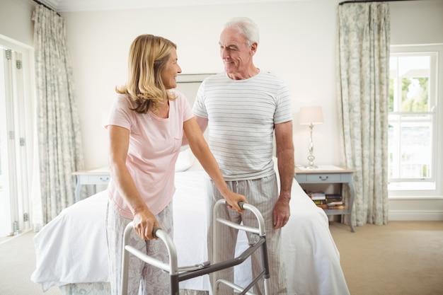 Donna d'aiuto dell'uomo senior da camminare con il camminatore