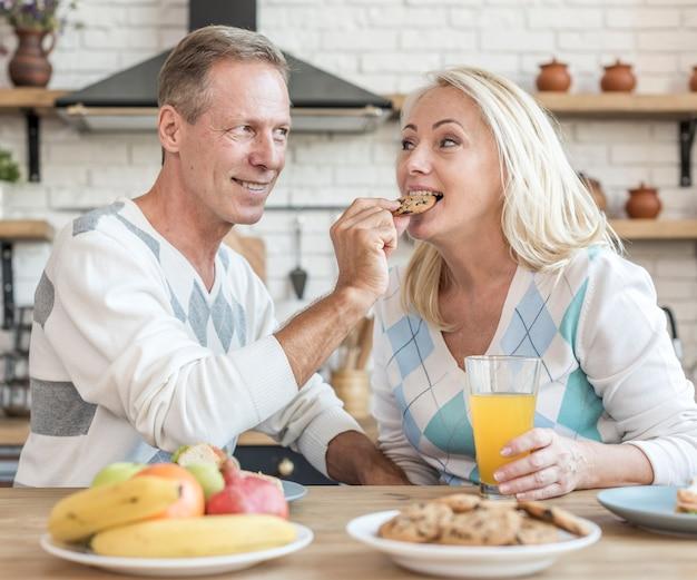 Donna d'alimentazione dell'uomo felice del colpo medio