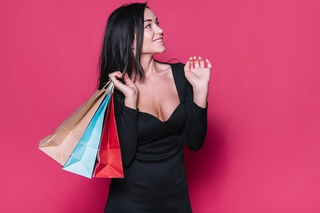 Donna d'avanguardia in abito nero con borse della spesa