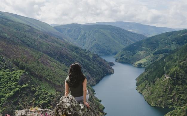 Donna da dietro guardando il fiume.