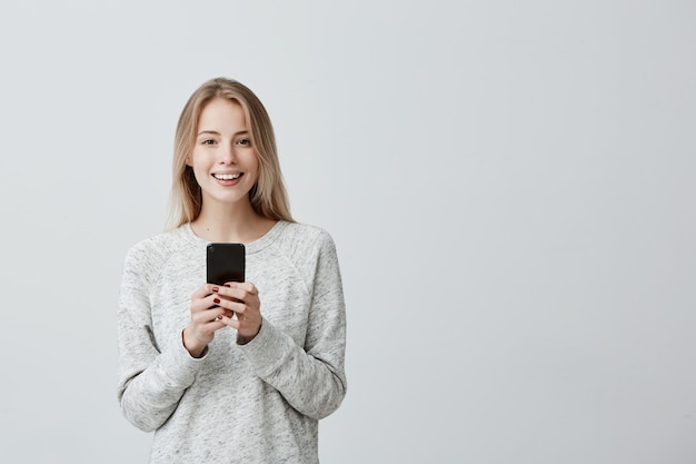 Donna dai capelli biondi felice positiva con ampio sorriso tramite cellulare, felice di ricevere un messaggio con una buona notizia, controllando il feed delle notizie sui suoi account di social network. tecnologie e comunicazione moderne