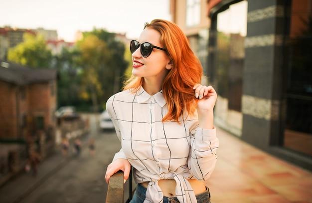 Donna dai capelli rossi attraente in occhiali che indossa sulla camicetta bianca