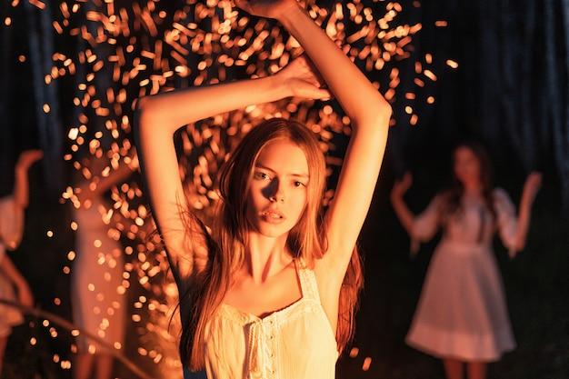 Donna dai capelli rossi che balla davanti a un fuoco