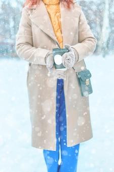 Donna dai capelli rossi in cappotto, maglione giallo, pantaloni blu, muffole beve caffè per andare