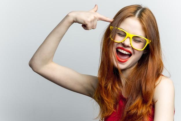 Donna dai capelli rossi in un vestito rosso e occhiali gialli, bianchi