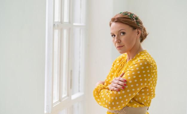 Donna dai capelli rossi solitaria in abito giallo si abbraccia