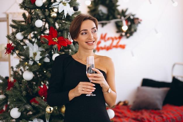 Donna dall'albero di natale che beve champaigne