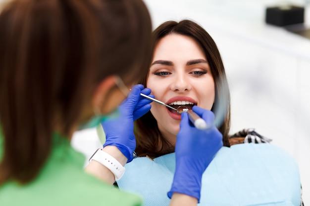 Donna dall'odontoiatria il dentista tratta i denti per il suo bel paziente. l'odontoiatra perfora i denti del paziente