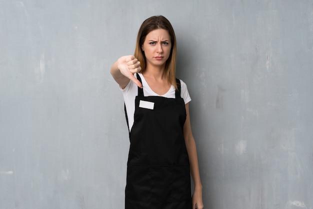 Donna degli impiegati che mostra dowg del pollice con l'espressione negativa